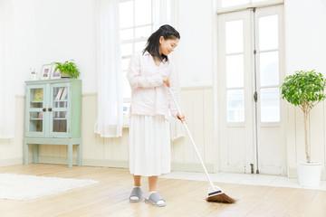 女性 掃き掃除 リビング