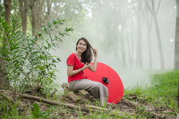 Beautiful Thai girl in Lanna traditional costume with red umbrel