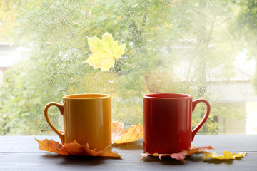 autumn warming atmosphere of comfort/ two cups on a table with leaves against the window with rain drops