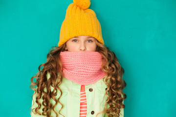 Cute little lady wearing yellow woolen cap and pink scarf agains