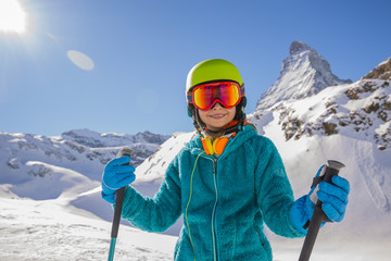 Teenage girl skiing in Swiss Alps in Sunny Day. Matterhorn in Ba