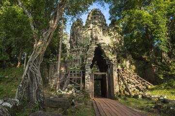 Scenic dappled jungle view of the Angkor Thom West Gate at the Angkor Temple complex near Siem Reap Cambodia