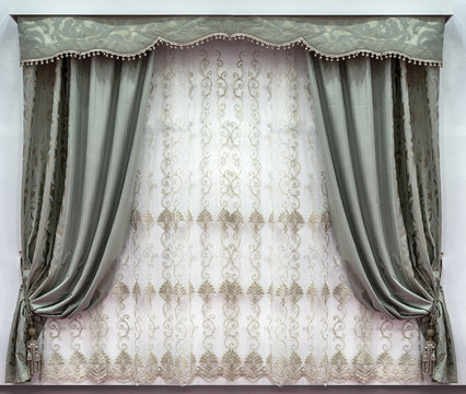 The stylish design of the windows in the interior. Combined curtains made of the natural fabrics. A hard pelmet and a tulle with embroidery