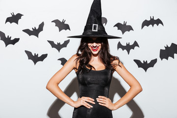 Happy gothic woman in witch halloween costume standing and smiling
