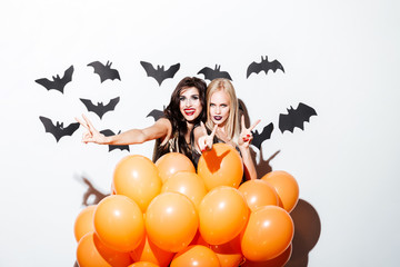 Two smiling women with vampire makeup and balloons having fun