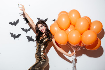 Cheerful woman with vampire makeup and orange balloons having fun