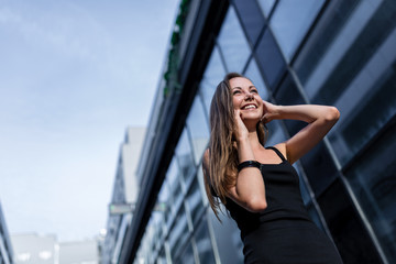 Happy Young Woman in Black Dress Talking on Cellphone in the City
