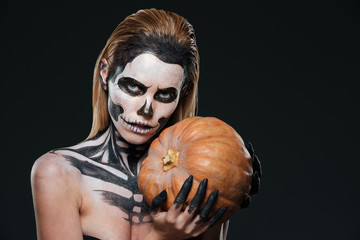 Woman with skeleton halloween makeup holding pumpkin