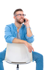 Young man sitting on chair and using mobile phone