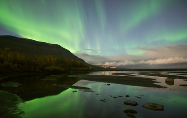 Northern lights dancing over calm lake in Abisko national park