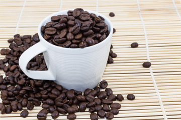 Coffee Cup with roasted coffee beans on heap of bamboo brown str