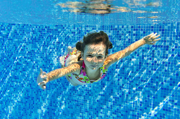 Child swims in pool underwater, happy active girl has fun under water, kid sport on family vacation