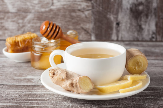 A white cup of green natural tea with ginger, lemon and honey on wooden rustic background. Healthy drink. Hot winter beverage concept.