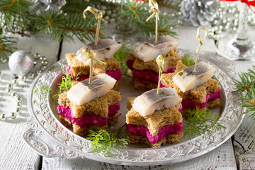 Canapes in the form of a star with pickled herring, beetroot and