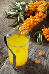 Autumn hot drink. Tea with sea-buckthorn berries branch on vinta