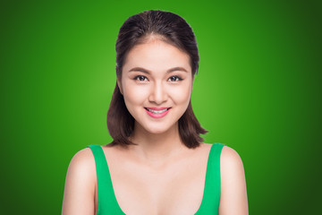 Beautiful asian woman smiling on green background.