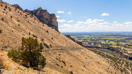 The road among the dry grass. The beautiful landscape of cliffs. Smith Rock state park, Oregon