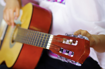 Closeup neck of beautiful acoustic guitar being tuned by woman sitting down, musician concept