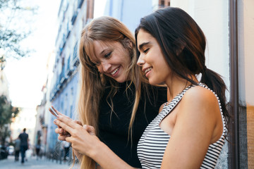 Two girls using a phone in the street