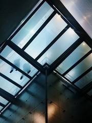 Low Angle View Of People Walking On Transparent Flooring