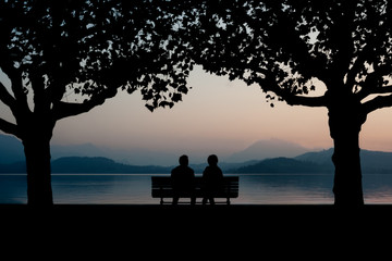 Silhouette Couple Sitting On Bench By Calm Lake At Dusk