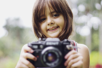 Portrait of smiling girl holding camera