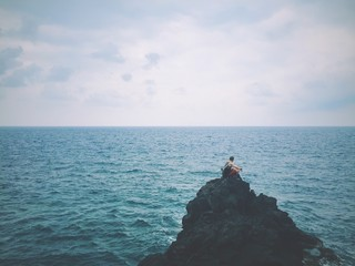 Man Sitting On Rock In Middle Of Sea Against Sky
