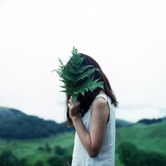 Side View Of Young Woman Covering Face With Leaves