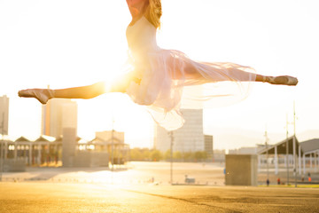 Ballet dancer performing ballet on the street during sunrise