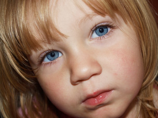 Portrait of a little blonde girl with blue eyes
