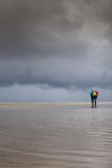 Paar mit Regenschirm vor Wolkenfront am Strand