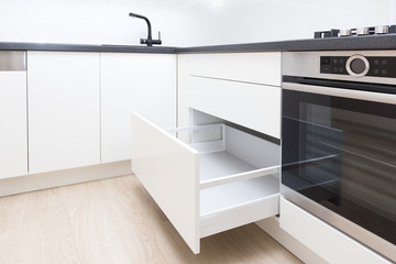 Fototapeta Opened white drawer in a kitchen cabinet with an handleless front, tip to open system obraz