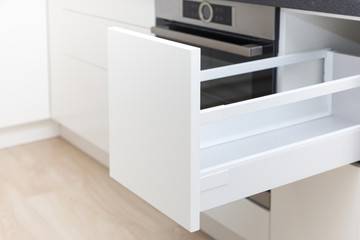 Opened white drawer in a kitchen cabinet with an handleless front, tip to open system