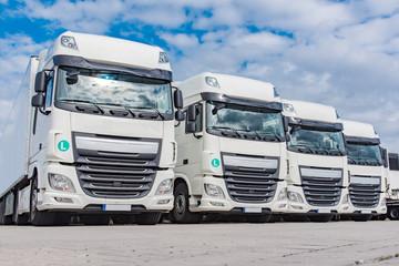 Spedition - Logistik , vier weiße LKW`s geparkt