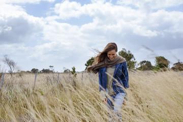 Happy woman walking on field against sky