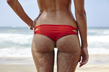 Rear view midsection of woman in red bikini bottom at beach