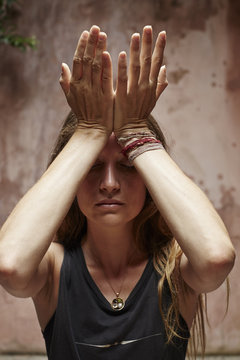 Woman meditating with hands on forehead