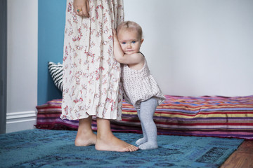 Portrait of baby girl holding mother and standing on floor at home