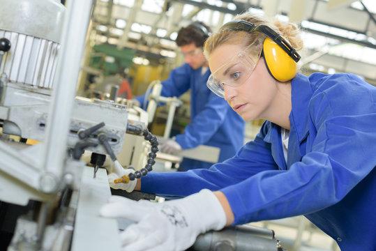 Woman using industrial machine