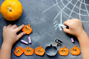 Happy halloween! Child draws with chalk spider web on the table