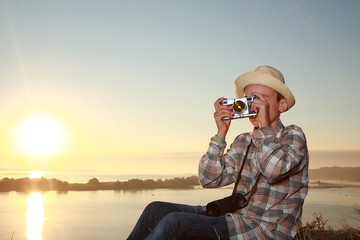 мальчик фотографирует на закате солнца