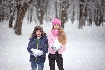 The children - a boy and a girl playing in the street during a snowfall