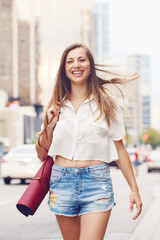 Portrait of smiling happy slim fit sporty young white Caucasian hippie hipster woman with long blond hair going with yoga mat on busy city street among cars, healthy lifestyle concept.