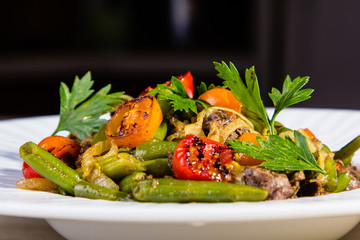 grilled meats and vegetables (tomatoes, beans, onion) are on the