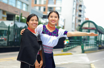 Beautiful hispanic mother and daughter wearing traditional andean clothing, waiting for bus at public station while interacting together, smiling happily, outdoors environment