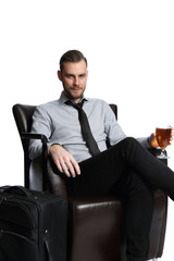 Attractive businessman with a beer and his bag on the side, sitting down in a lounge chair on his way to make business. White background.