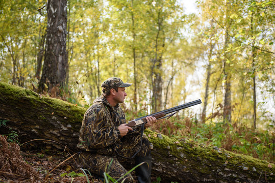 Hunter with a gun in the autumn woods, hunting for a hazel grouse