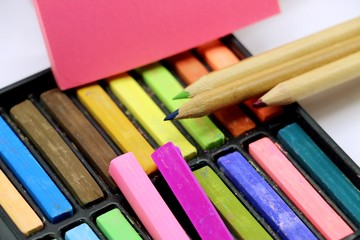 Back to school theme , there are colourful items, chalk, pencils, blank paper