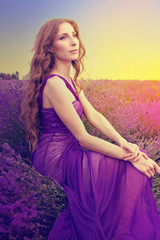 Young woman with long blonde hair in a purple dress looking at t