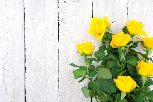 Bouquet of yellow roses on rustic wooden background. Valentine's